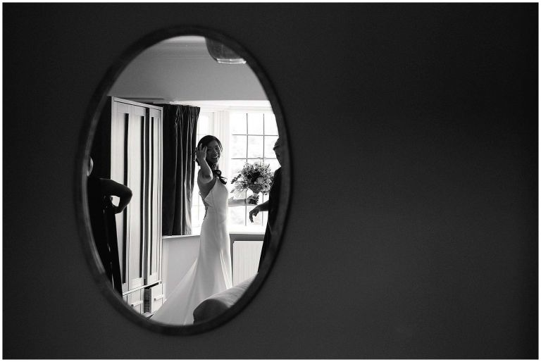 Candid black and white image taken in mirror of bride