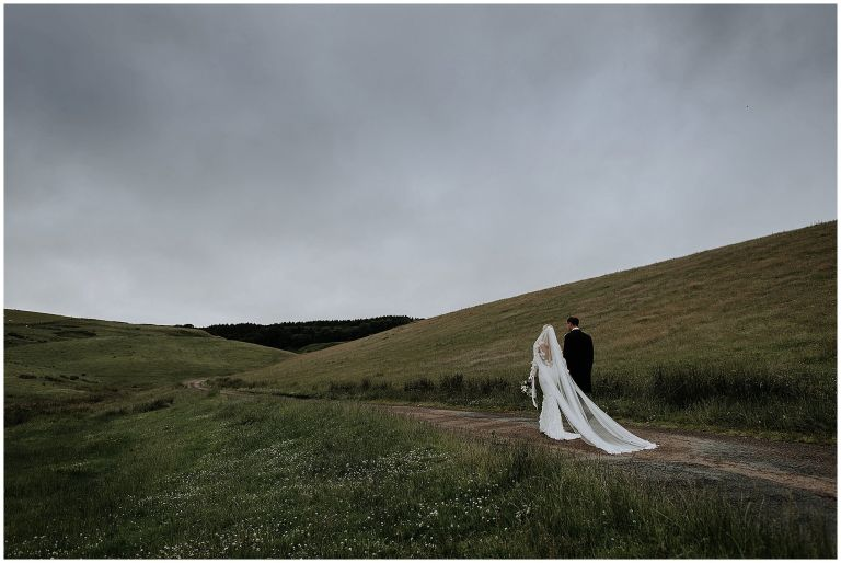 Landscape shot with bride and groom walking along country road surrounded by hills and the Northumbrian landscape