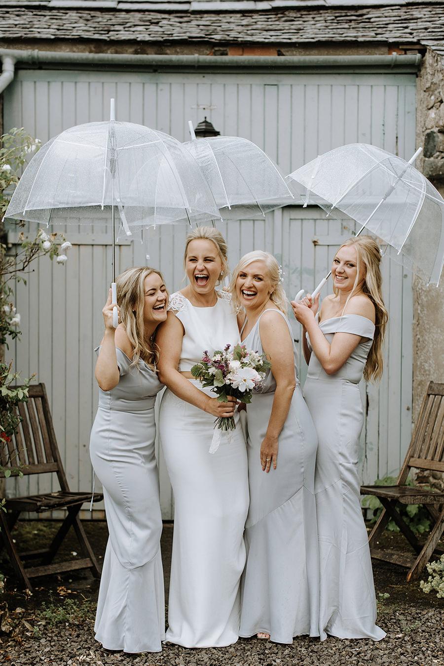 fun bride and bridesmaids shot with umbrellas