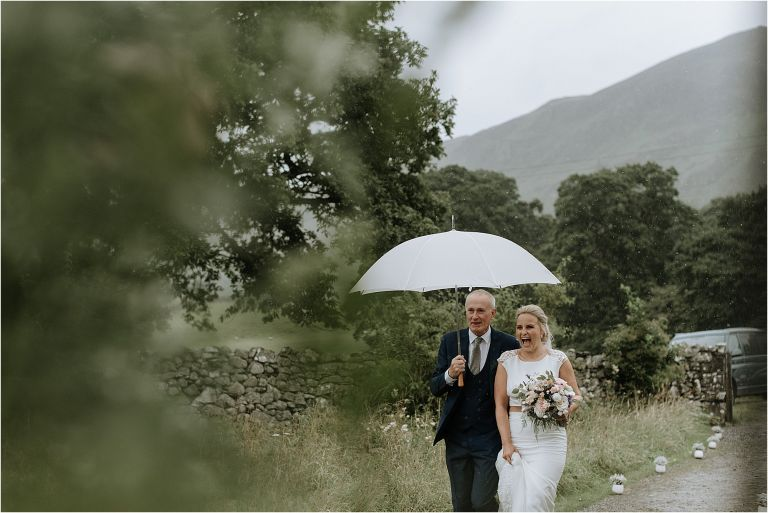 bride and dad walking to church under brolly