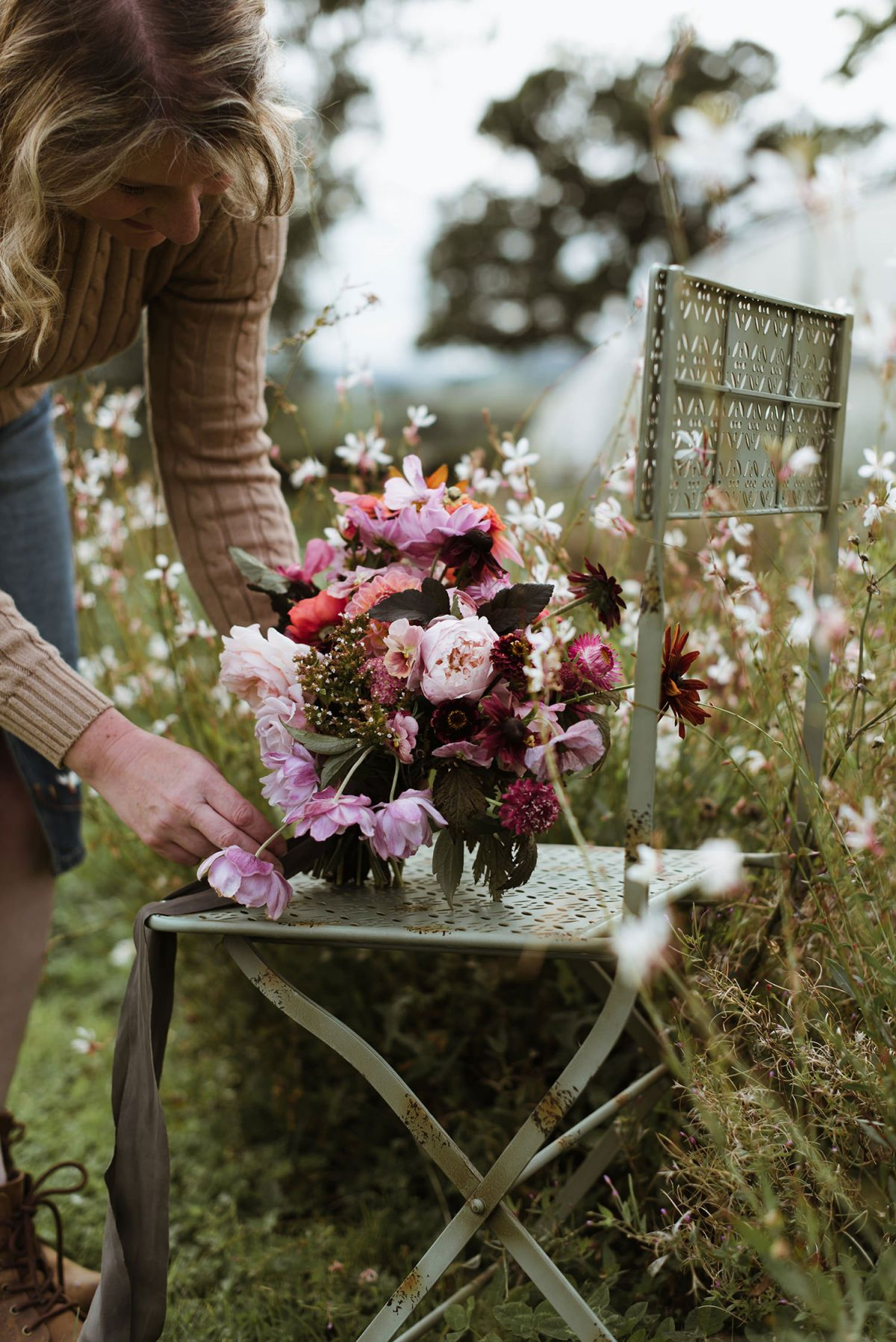 Close up of stylist placing flowers on chair
